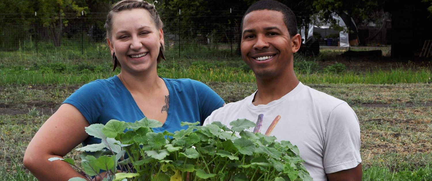 Smiling people holding seedlings on The Farm at SOU
