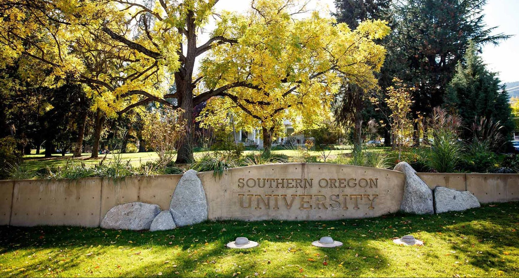 Rock sign at Southern Oregon University - Trees and grass in the background