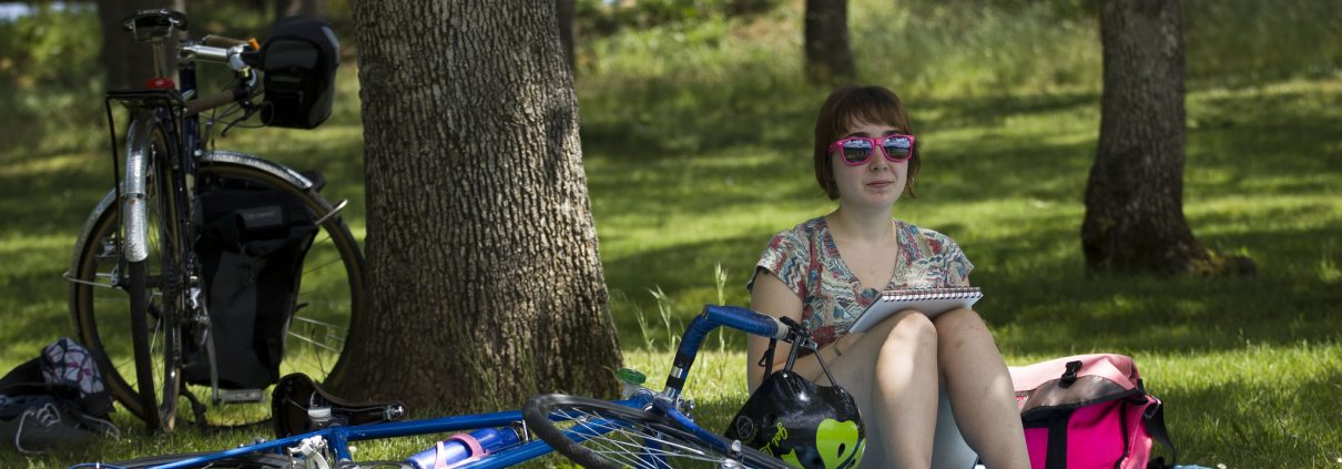 Girl with bike sitting in shade